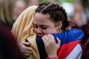 Students comfort each other during a vigil in Christchurch on March 18, 2019, three days after a shooting incident at two mosques in the city that claimed the lives of 50 Muslim worshippers. - New Zealand will tighten gun laws in the wake of its worst modern-day massacre, the government said on March 18, as it emerged that the white supremacist accused of carrying out the killings at two mosques will represent himself in court.