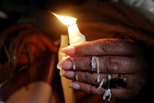 A woman with melted wax on her fingers holds a candle during a candlelight vigil for the victims of the Christchurch mosque attacks in New Zealand, in Islamabad, Pakistan March 18, 2019. REUTERS/Akhtar Soomro