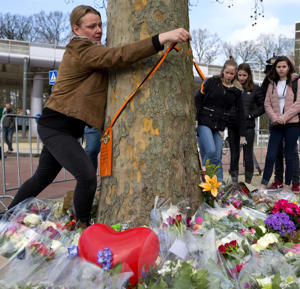 "A woman attaches a sign to a tree reading ""The empty space, it hurts so much, but Rinke will be always with us in our thoughts"", referring to one of three victims, at the site of a shooting incident in a tram in Utrecht, Netherlands, Tuesday, March 19, 2019. A gunman killed three people and wounded others on a tram in the central Dutch city of Utrecht Monday March 18, 2019. (AP Photo/Peter Dejong)"