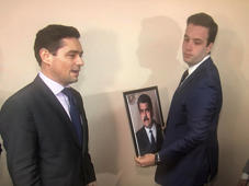 Carlos Vecchio (L), the envoy to the United States of Venezuelan opposition leader Juan Guaido, and an aide take down a picture of Venezuela's President Nicolas Maduro and replace it with a picture of Guaido in this frame grab from video after supporters of Guaido took control of the office of Venezuela's military attache in Washington, U.S. March 18, 2019.   REUTERS/Gershon Peaks