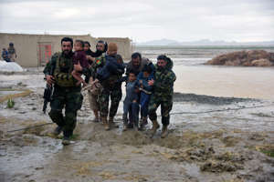 Afghan Security forces carry children after flood affected their homes in Arghandab district of Kandahar province, on March 2, 2019.