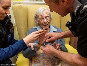 This is the moment 104-year-old Anne Brokenbrow, pictured along with PCSO Kelly Foyle, right, and PC Stephen Harding, left, is 'arrested' at the Stokeleigh Care Home in Bristol today