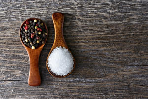 Two wooden spoons with sea salt and peppercorns