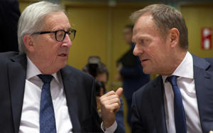European Commission President Jean-Claude Juncker, left, speaks with European Council President Donald Tusk during a tripartite social summit at the Europa building in Brussels, Wednesday, March 20, 2019. European Union officials received a letter from British Prime Minister Theresa May requesting a Brexit extension and they hope to have more clarity about her intentions by Thursday. (AP Photo/Virginia Mayo)
