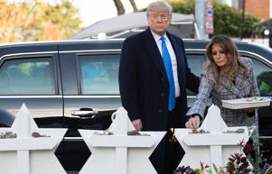 US President Donald Trump and First Lady Melania Trump place stones and flowers on a memorial as they pay their respects at the Tree of Life Synagogue following last weekend's shooting in Pittsburgh, Pennsylvania, October 30, 2018. - Scores of protesters took to the streets of Pittsburgh to denounce a visit by US President Donald Trump in the wake of a mass shooting at a synagogue that left 11 people dead. Demonstrators gathered near the Tree of Life synagogue, where the shooting took place, holding signs that read 'President Hate, Leave Our State!' and 'Trump, Renounce White Nationalism Now.' (Photo by SAUL LOEB / AFP)        (Photo credit should read SAUL LOEB/AFP/Getty Images)