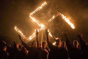 "Supporters of the National Socialist Movement, a white nationalist political group, give Nazi salutes while taking part in a swastika burning at an undisclosed location in Georgia, U.S. on April 21, 2018. Reuters photographer Go Nakamura: ""I never fathomed capturing this image. Earlier in the day, I had been covering a very uneventful white supremacy rally in Newnan, Georgia, run by a neo-Nazi group called National Socialist Movement, the same group involved in the infamous Charlottesville rally in 2017. A couple of colleagues told me that the group might hold some sort of secret ritual outside of town afterwards. Together, we approached the head of the movement who granted us permission to document the ritual. After waiting for several hours, we reached the backyard of a bar in the middle of nowhere where we saw a big wooden swastika and cross set up on the ground. Then, a group of some 15 neo-Nazis lit up their torches as they encircled the swastika and performed a Nazi salute. It was surreal. Adrenalin was rushing through my body, but I remained focused on capturing what was unfolding in front of my eyes. The ritual reached its climax when the group lined up in front of the burning swastika and began chanting and performing a final salute. We left immediately after it ended. As we drove away, I set about unravelling the tangle of emotions I experienced that day that led to this photo."" REUTERS/Go Nakamura  SEARCH ""POY STORY"" FOR THIS STORY. SEARCH ""REUTERS POY"" FOR ALL BEST OF 2018 PACKAGES. TPX IMAGES OF THE DAY."