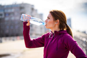 Young woman with headphones drinking water during jogging outdoors in the morning.