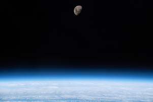 A waxing gibbous Moon is seen above Earth's limb as the International Space Station was orbiting 266 miles above the South Atlantic Ocean.
