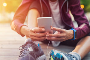 Closeup sporty woman hand using smartphone while sitting on floor. Woman wearing jacket and typing on mobile phone to check pulse rate in the early morning. Runner hand using smart phone while sitting on ground after running.