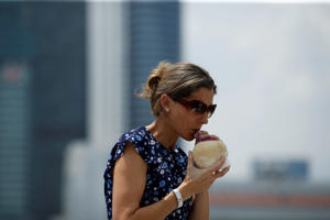 SINGAPORE - OCTOBER 21:  WTA Legend Monica Seles enjoys fresh Coconut juice and poses for a photo at the Courtside by the Bay at Marina Bay Sands on October 21, 2018 in Singapore.  (Photo by Yong Teck Lim/Getty Images for the WTA)