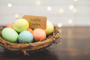 Woven stick basket of colored eggs with handmade Happy Easter sign.