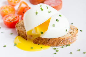 Poached egg on piece of wholegrain bread with vegetables and herbs close up