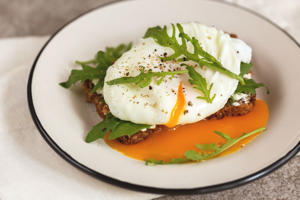 Rye bread toast with poached egg, dairy cream, spices and arugula and cup of coffee on the gray slate background. Continental breakfast. Healthy food concept. Selective focus. Horizontal view. Copy space