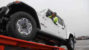 a truck is parked in front of a car: Jeep Gladiator Delivery Start