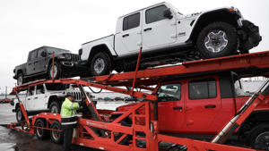 a red and black truck sitting on top of a car: Jeep Gladiator Delivery Start