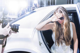 famous celebrity getting out of a limousine in front of a red carpet event, with flashing paparazzi