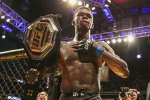Israel Adesanya holds up the belt after defeating Kelvin Gastelum by unanimous decision in their interim middleweight championship bout during the UFC 236 event at State Farm Arena on April 13, 2019 in Atlanta, Georgia.