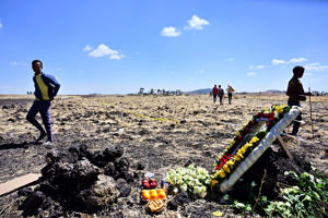 People walk by a commemorative wreath and fruits left by relatives of victims at the crash site of an Ethiopian airways operated Boeing 737 MAX aircraft on March 16, 2019 at Hama Quntushele village near Bishoftu in Oromia region. - A French investigation into the March 10 Nairobi-bound Ethiopian Airlines Boeing 737 MAX crash that killed 157 passengers and crew opened on March 15 as US aerospace giant Boeing stopped delivering the top-selling aircraft.