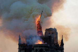 The steeple engulfed in flames collapses as the roof of the Notre-Dame de Paris Cathedral burns on April 15, 2019 in Paris. - A colossal fire swept through the famed Notre-Dame Cathedral in central Paris on April 15, 2019, causing a spire to collapse and raising fears over the future of the nearly millenium old building and its precious artworks. The fire, which began in the early evening, sent flames and huge clouds of grey smoke billowing into the Paris sky as stunned Parisians and tourists watched on in sheer horror. (Photo by Geoffroy VAN DER HASSELT / AFP)        (Photo credit should read GEOFFROY VAN DER HASSELT/AFP/Getty Images)