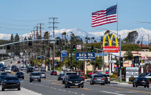 ORANGE, CA - MARCH 14: With fresh snow on the San Gabriel mountains in the background and Santa Ana winds blowing throughout Orange County, a large America flag stands out straight from its flagpole as traffic passes by on Tustin Avenue in Orange on Thursday, March 14, 2019. Photo by Mark Rightmire/MediaNews Group/Orange County Register via Getty Images