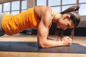 Side view of attractive young woman doing core exercise on fitness mat in the gym. Female doing press-ups in health club.
