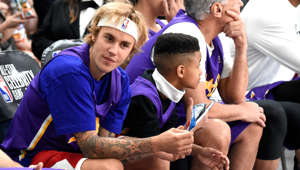 LOS ANGELES, CA - FEBRUARY 16:  (L-R) Recording artist Justin Bieber, Demarjay Smith, Marc Lasry, and Kris Wu sit during the NBA All-Star Celebrity Game 2018 presented by Ruffles at Verizon Up Arena at LACC on February 16, 2018 in Los Angeles, California.  (Photo by Kevin Mazur/WireImage)