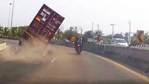 Motorcyclist narrowly avoids being crushed by huge truck