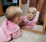 Adorable baby befriends her reflection in the mirror