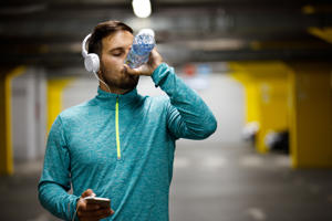 Man is drinking water and relaxing after jogging.