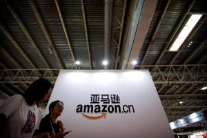 Visitors walk past a logo for Amazon China at the Beijing International Book Fair in Beijing, Wednesday, Aug. 23, 2017. The fair, which draws Chinese and international publishers, runs until Aug. 27. (AP Photo/Mark Schiefelbein)