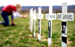A woman looks at a line of crosses commemorating those killed in the Columbine High School shooting on the 20th anniversary of the attack in Littleton, Colorado, U.S., April 20, 2019.
