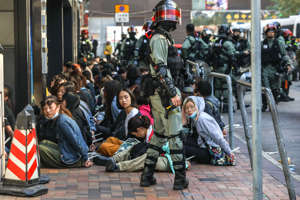 People are detained by police near the Hong Kong Polytechnic University in Hung Hom district of Hong Kong on November 18, 2019. - Pro-democracy demonstrators holed up in a Hong Kong university campus set the main entrance ablaze November 18 to prevent surrounding police moving in, after officers warned they may use live rounds if confronted by deadly weapons.