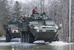Members of the Canadian armed forces patrol a street surrounded by floodwaters in the town of Rigaud, Que, west of Montreal, Sunday, April 21, 2019.