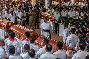NEGOMBO, SRI LANKA - APRIL 23: A member of the clergy walks between coffins during a mass funeral at St Sebastian Church on April 23, 2019 in Negombo, Sri Lanka. At least 311 people were killed with hundreds more injured after coordinated attacks on churches and hotels on Easter Sunday rocked three churches and three luxury hotels in and around Colombo as well as at Batticaloa in Sri Lanka. Sri Lankan authorities declared a state of emergency on Monday as police arrested 24 people so far in connection with the suicide bombs, which injured at least 500 people as the blasts took place at churches in Colombo city as well as neighboring towns and hotels, including the Shangri-La, Kingsbury and Cinnamon Grand. (Photo by Carl Court/Getty Images)