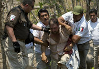 A Central American migrant is detained by Mexican immigration agents on the highway to Pijijiapan, Mexico, Monday, April 22, 2019. Mexican police and immigration agents detained hundreds of Central American migrants Monday in the largest single raid on a migrant caravan since the groups started moving through Mexico last year. (AP Photo/Moises Castillo)
