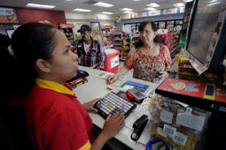 An employee of Femsa's Oxxo convenience store serves customers at a store in Monterrey, Mexico August 27, 2018. Picture taken August 27, 2018. REUTERS/Daniel Becerril