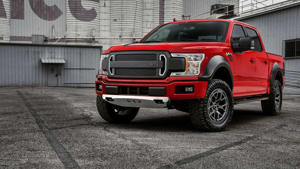 a red and black truck parked in front of a car: Ford F-150 RTR