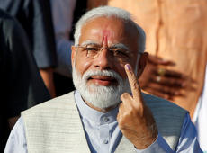 India's Prime Minister Narendra Modi shows his ink-marked finger after casting his vote outside a polling station during the third phase of general election in Ahmedabad, India, April 23, 2019. REUTERS/Amit Dave