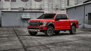 a red and black truck parked in front of a house: Ford F-150 RTR