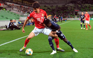 Guangzhou player Gao Zhunyi (L) is tackled by Melbourne Victory player Elvis Kamsoba (C) in the AFC Champions League football match between Australian club Melbourne Victory and Guangzhou Evergrande of China in Melbourne on April 23, 2019. (Photo by WILLIAM WEST / AFP) / -- IMAGE RESTRICTED TO EDITORIAL USE - STRICTLY NO COMMERCIAL USE --        (Photo credit should read WILLIAM WEST/AFP/Getty Images)