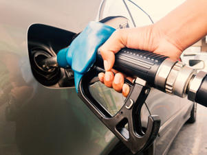 Hand holding gasoline nozzle for car refueling at gas station