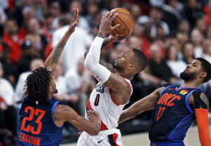 Portland Trail Blazers guard Damian Lillard, center, shoots between Oklahoma City Thunder guard Terrance Ferguson, left, and forward Paul George, right, during the second half of Game 5 of an NBA basketball first-round playoff series, Tuesday, April 23, 2019, in Portland, Ore. The Trail Blazers won 118-115. (AP Photo/Craig Mitchelldyer)