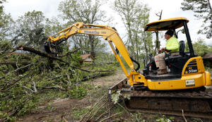 Terrill Harvey, right, uses his heavy machinery to remove debris from a friend's home, Friday, April 19, 2019, in Morton, Miss., as residents begin their cleanup from Thursday's possible tornado touchdown that heavily damaged many homes. Strong storms again roared across the South on Thursday, topping trees and leaving a variety of damage in Mississippi, Louisiana and Texas. (AP Photo/Rogelio V. Solis)