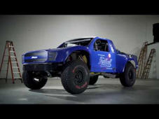 a car parked in front of a truck: Get a closer look at Jimco Racing's Spec Trophy Truck for built for Fastball Racing. More at: http://bit.ly/FastballRacing