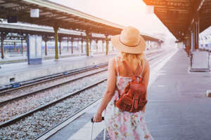 Woman traveler with baggage, passenger waiting for the train on platform