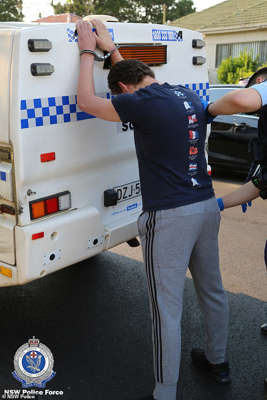 a person standing in front of a truck: The accused (pictured during Wednesday's arrest) also allegedly downloaded a document on how to use knives and other blunt instruments in a terrorist attack