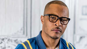 T.I. wearing glasses and a blue shirt