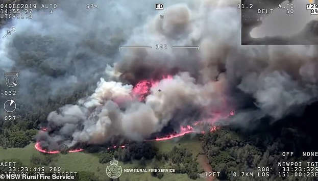 a train on a track with smoke coming out of it: Firefighters are bracing for another day of horror in New South Wales as the threat of two giant blazes combining looms. Wisemans Ferry fire pictured