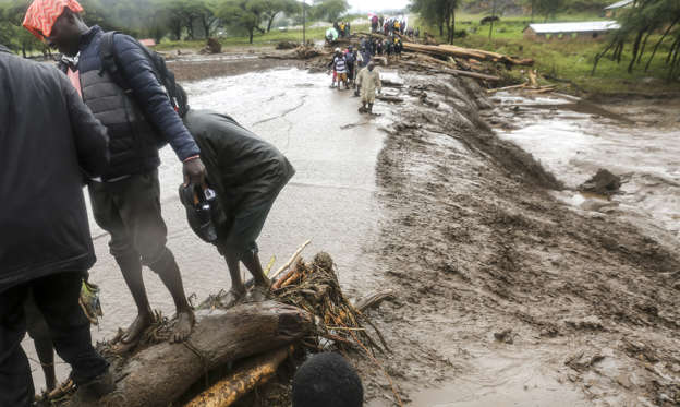 Slide 1 of 52: Passengers from stranded vehicles cross floodwaters on foot, on the road from Kapenguria, in West Pokot county, in western Kenya Saturday, Nov. 23, 2019. Kenya's interior minister says dozens of people have been killed in mudslides, after heavy rains unleashed overnight floods in western Kenya.