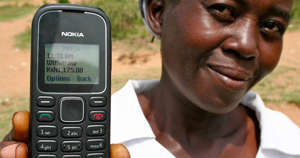a close up of a person holding a cell phone: M-PESA's pretty cool.